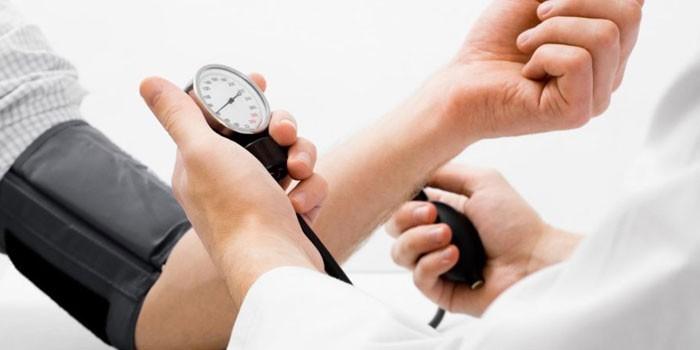 Медик измеряет давление человеку