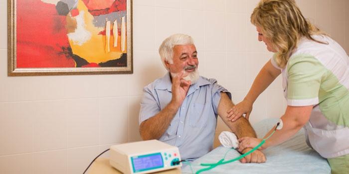 Пожилой мужчина на физиотерапевтической процедуре