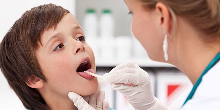 Медсестра смотрит горло мальчику