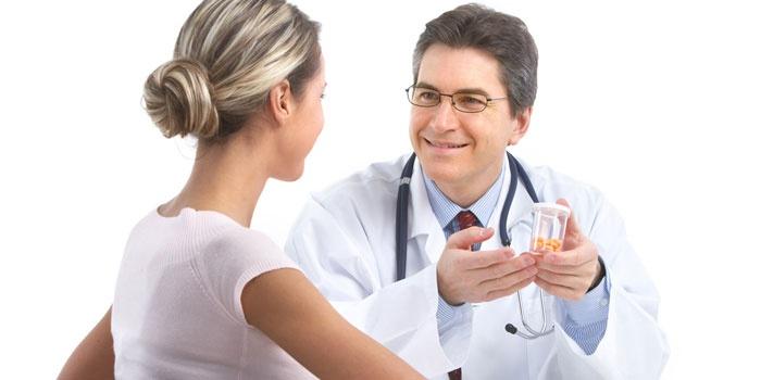 Врач объясняет девушке схему приема препаратов