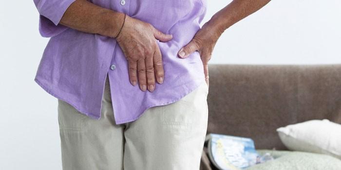 Пожилая женщина держится руками за тазобедренный сустав