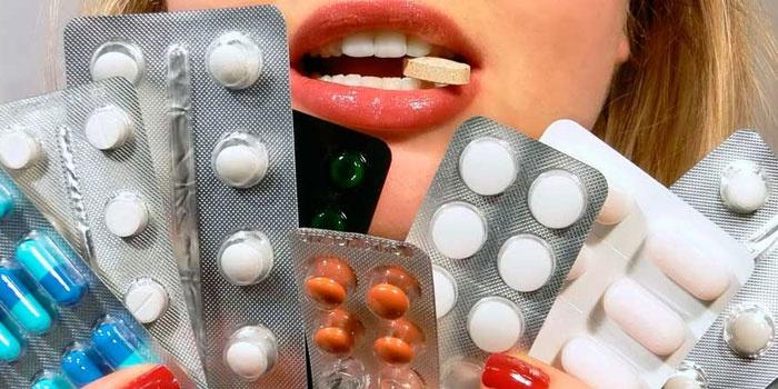 Девушка держит таблетки и капсулы