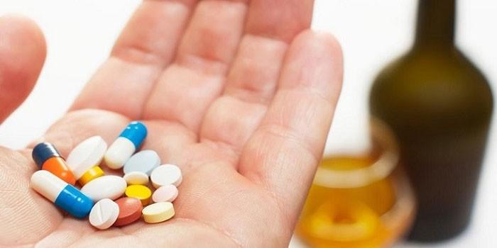 Медикаменты на ладони и алкоголь