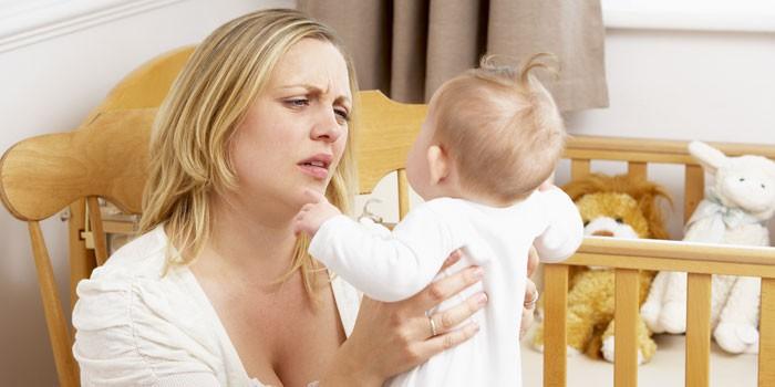 Женщина держит на руках грудного ребенка