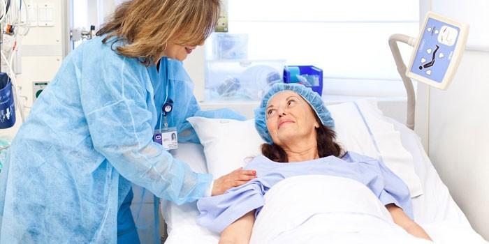 Женщина в больничной палате и медсестра