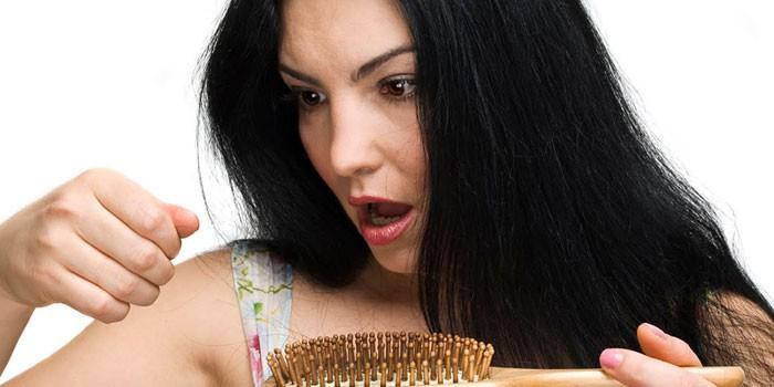 Девушка смотрит на выпавшие волосы на расческе