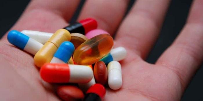 Таблетки и капсулы на ладони