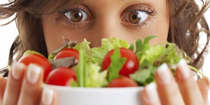 Девушка держит перед собой тарелку с салатом