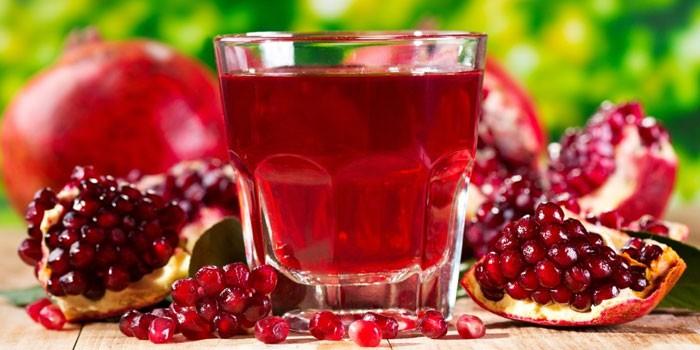 Гранатовый сок в стакане и гранаты