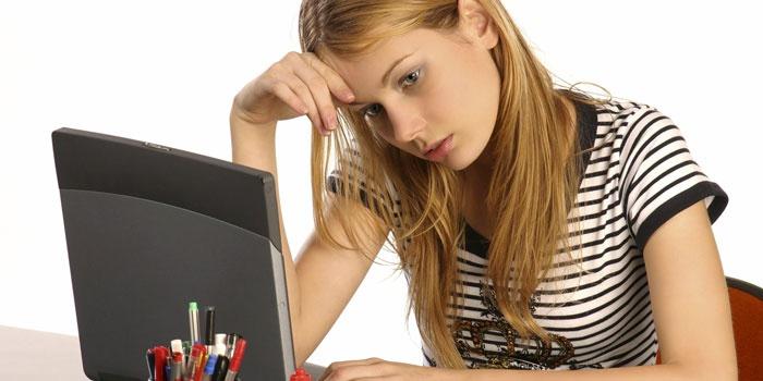 Уставшая девушка сидит за ноутбуком