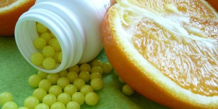 Аскорбиновая кислота в драже и половина апельсина