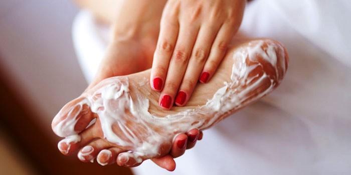 Женщина наносит крем на ногу