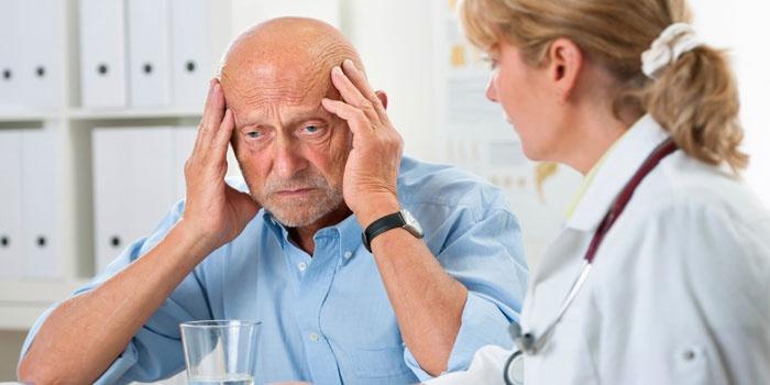 Пожилой мужчина жалуется врачу на головную боль