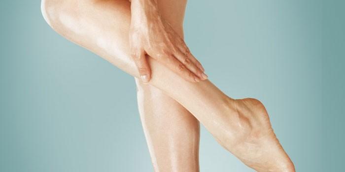 Женщина держится рукой за икроножную мышцу