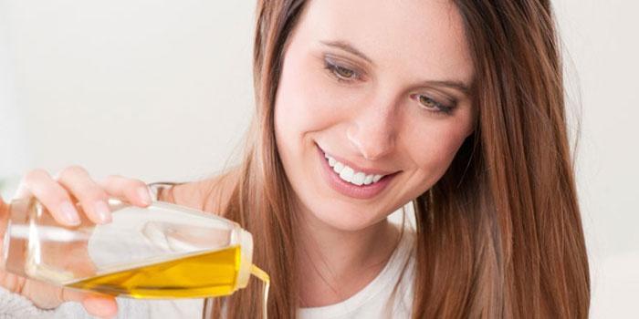 Девушка льет масло из бутылочки