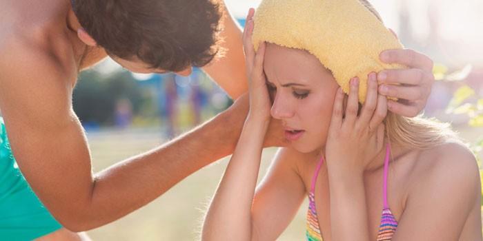 Парень прикладывает мокрое полотенце к голове девушки