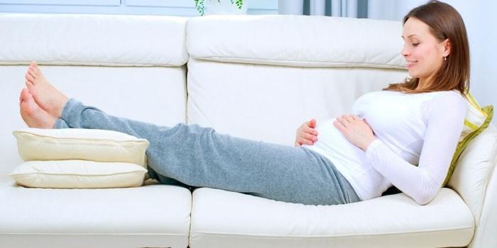 Беременная девушка лежит на диване