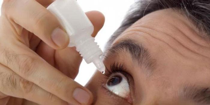Мужчина капает капли в глаз