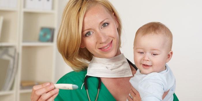 Врач измеряет температуру у малыша перед прививкой