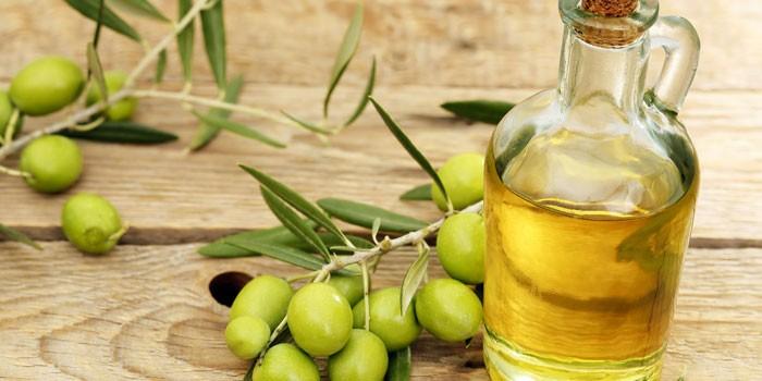Оливковое масло в стеклянном сосуде и оливки