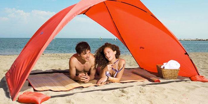 Мужчина и женщина на пляже под тентом