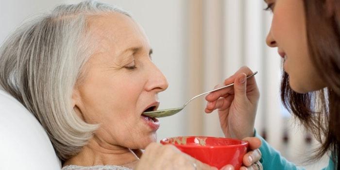 Девушка кормит пожилую женщину