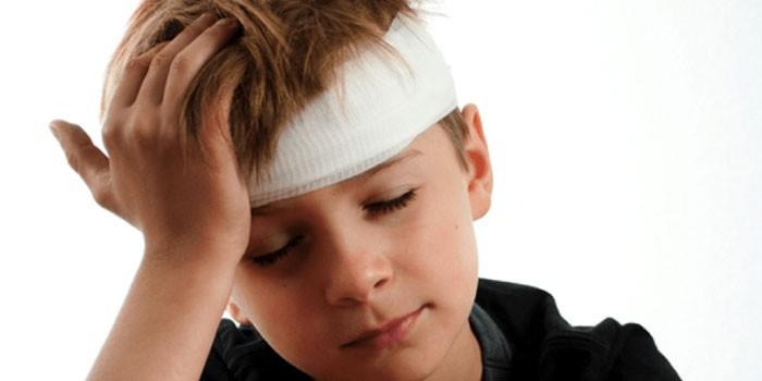 Мальчик держится за перебинтованную голову