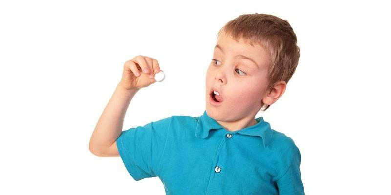 Мальчик держит в руке таблетку