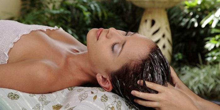 Девушке делают массаж головы с маслами