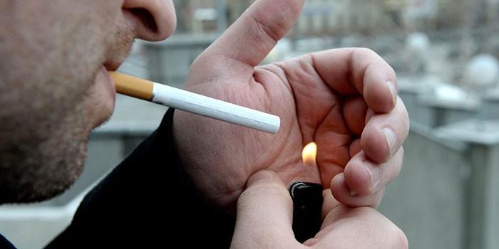 Мужчина прикуривает сигарету