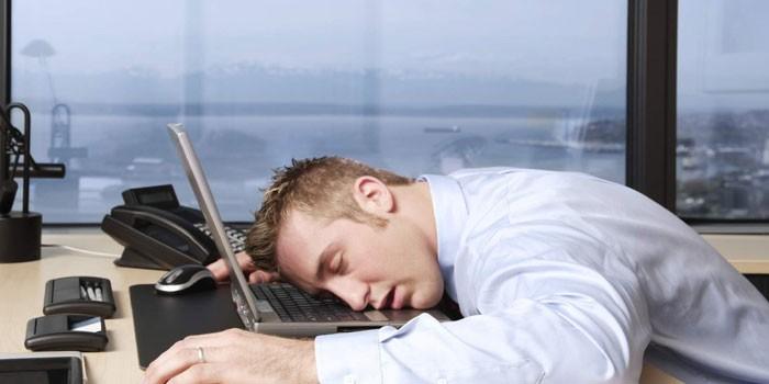 Мужчина спит на рабочем мечте