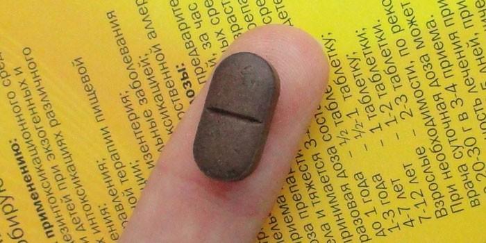 Таблетка Фильтрум на пальце