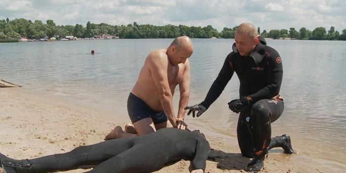 Инструктор обучает мужчину реанимационным действиям при утоплении