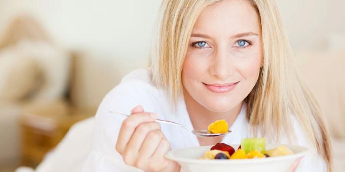 Девушка ест фруктовый салатом