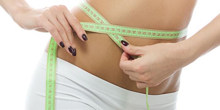 Девушка измеряет объем талии