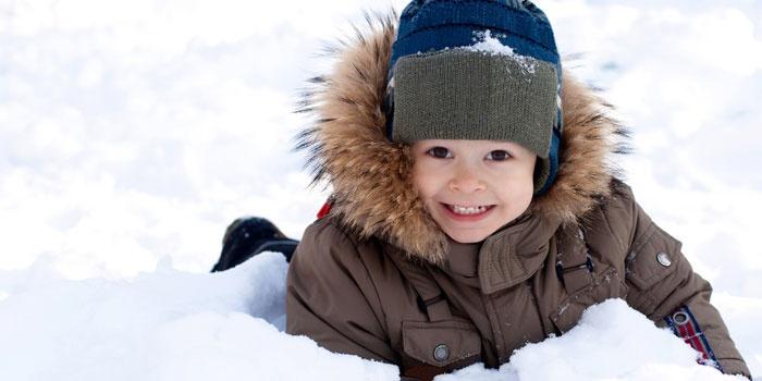 Ребенок лежит на снегу