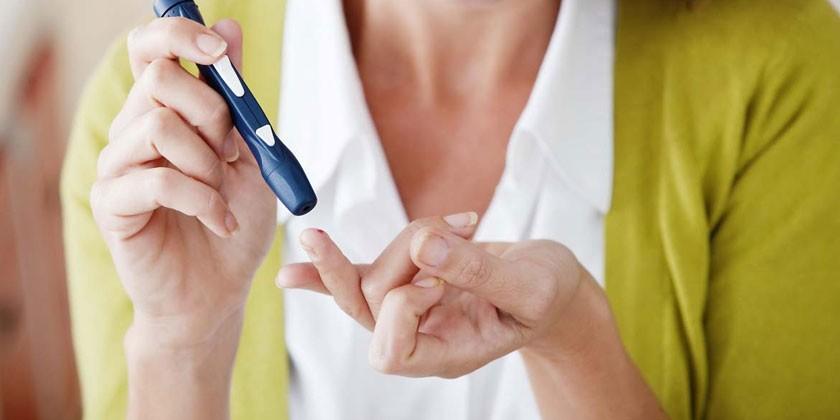 Женщина измеряет уровень сахара в крови глюкометром