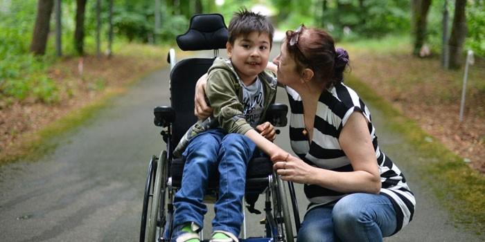 Женщина с ребенком в инвалидной коляске