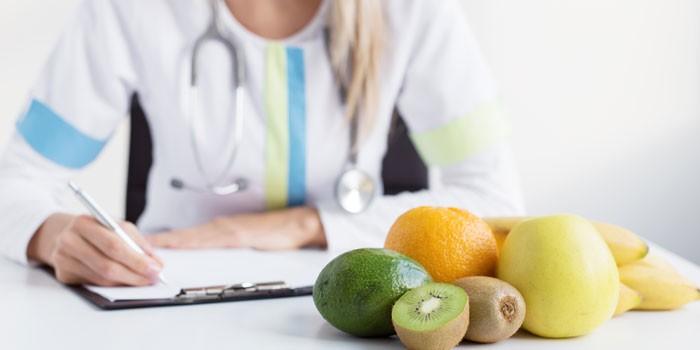 Врач пишет и фрукты на столе