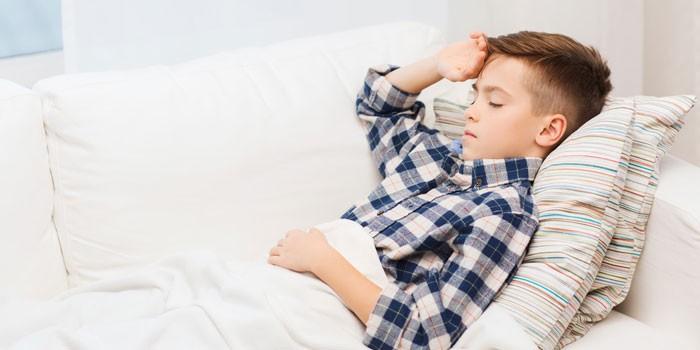 Мальчик лежит на диване