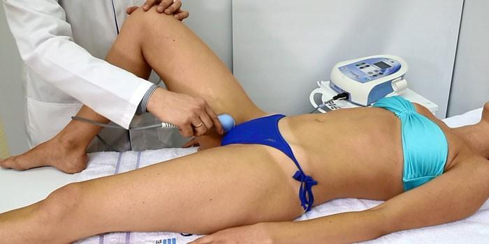 Девушке делают физиопроцедуру на тазобедренный сустав