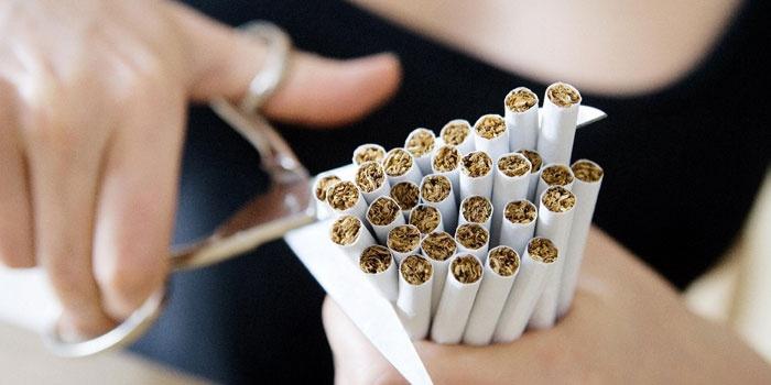 Девушка перерезает ножницами сигареты