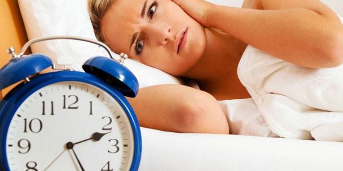 Девушка лежит в постели и часы