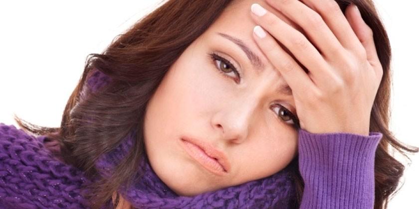 Молодая женщина держится за голову