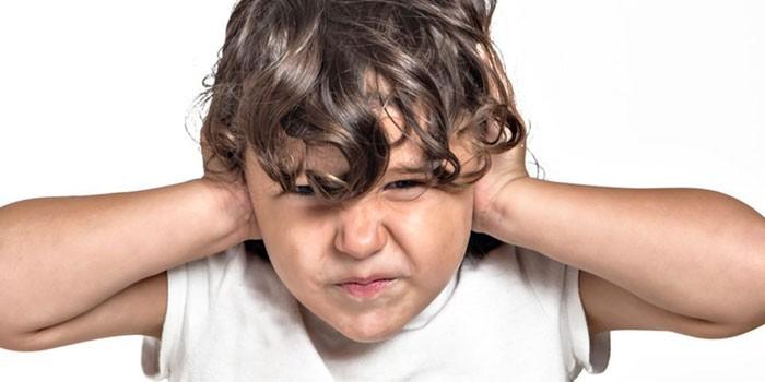 Мальчик закрывает уши ладонями