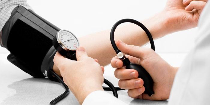 Медик измеряет артериальное давление