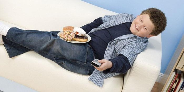Ребенок сидит с едой на диване