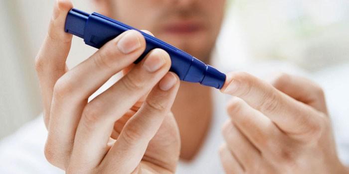 Мужчина измеряет сахар в крови глюкометром