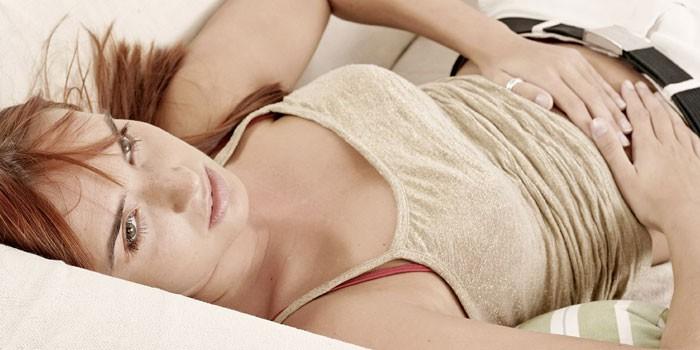 Девушка лежит на диване и держит руки на животе