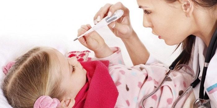 Медик измеряет девочке температуру